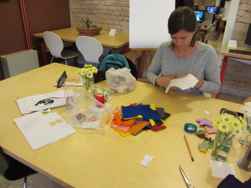 Спочатку за допомогою трафарету малюю на папері і вирізаю обрану фігурку, в моєму випадку ведмедик. А Катя теж творить - вирізає ялинку.