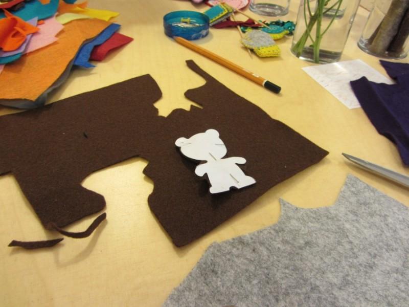 Тоді накладаю паперового ведмедика на тканину і прикріпляю до неї булавками. І знову ж таки вирізаю вже тканинного ведмедика.
